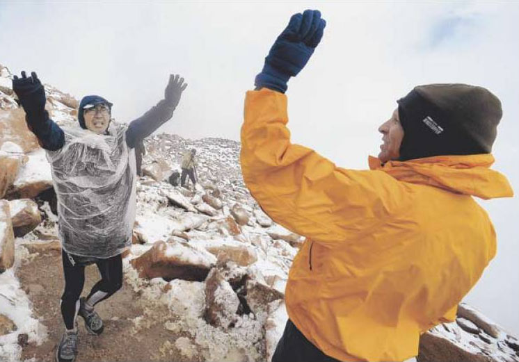 Kenichiro Maemura, left, of Novi, Mich., got congratulated by Mike Sandil as he was one of the last to reach the summit of Pikes Peak.