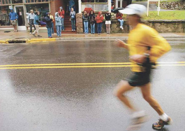 Spectators tried to stay dry under umbrellas and on porches Sunday as they cheered on runners during the Pikes Peak Marathon.