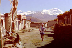 Matt Carpenter approaching the finish area of the first official world altitude marathon record (2:52:57) recognized by the Association of International Marathons (AIMS). The mountain in the background is Cho Oyu — the 6th highest in the world at 26,906 feet.
